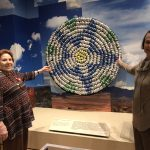 Adele and Vida pose by a sculpture created out of crushed cans to shed light on environmental and social issues.
